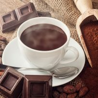 Cup of hot chocolate with cocoa powder, cocoa beans and pieces of chocolate.